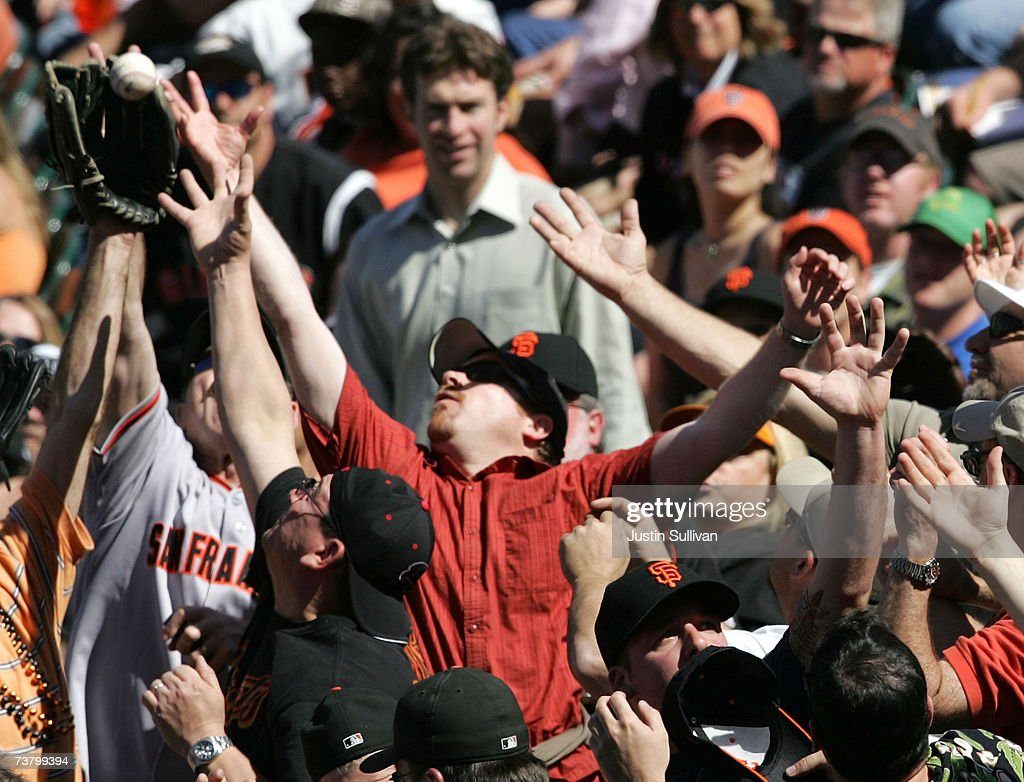 Fans of the San Francisco Giants reach for a foul ball during the game against the San Diego Padres on the Opening Day of Major League Baseball on April 3, 2007 at AT&T Park in San Francisco, California.