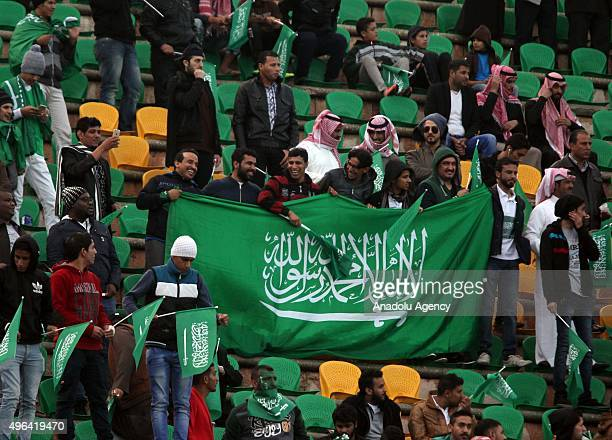Fans of the Saudi Arabian national team hold the national flag during the AFC qualifying Group A football match for the 2018 FIFA World Cup between...