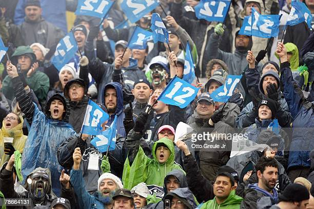 Fans of the Seattle Seahawks hold up the 12th man signs during the game against the Baltimore Ravens at Qwest Field on December 23, 2007 in Seattle,...