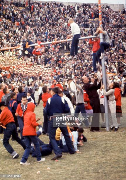 Fans of the Texas Longhorns celebrate and climb on the goal posts after the win against the Texas Christian University Horned Frogs after the rivalry...