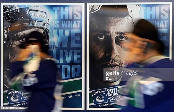 Fans of the Vancouver Canucks walk past a photo of Roberto Luongo prior to Game Five of the 2011 NHL Stanley Cup Final at Rogers Arena on June 10,...