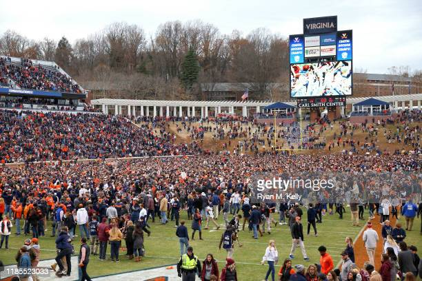 Fans of the Virginia Cavaliers rush the field after defeating the Virginia Tech Hokies during a game at Scott Stadium on November 29 2019 in...