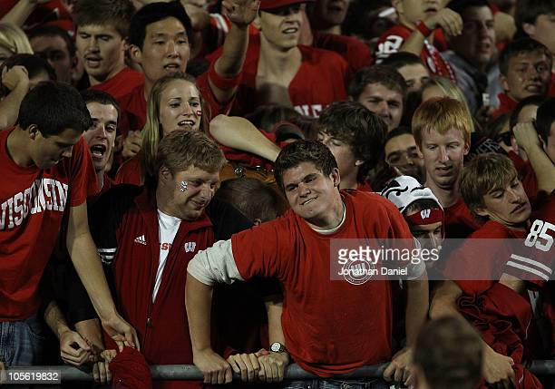 Fans of the Wisconsin Badgers located in the student section are pushed by the crowd from behind at the railing after a win against the Ohio State...