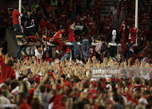Fans of the Wisconsin Badgers storm the field and climb the goal post after a win over the Ohio State Buckeyes at Camp Randall Stadium on October 16...
