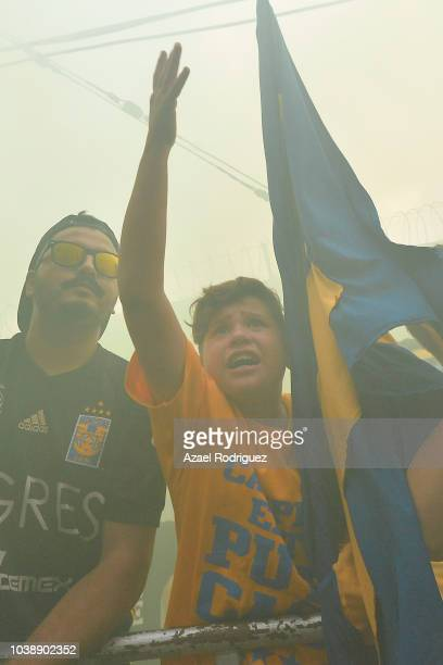 Fans of Tigres hold a banner to commemorate a fellow fan who recently passed away during the 10th round match between Tigres UANL and Monterrey as...