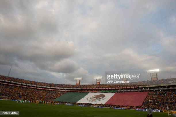 Fans of Tigres display a huge Mexican flag as they pay a minute of silence in memory of the victims of the September 19 earthquake in Mexico before...