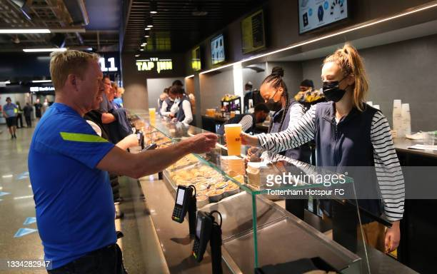 Fans of Tottenham Hotspur enjoy the pre-match atmosphere inside the stadium concourse as they purchase food and drink prior to the Premier League...