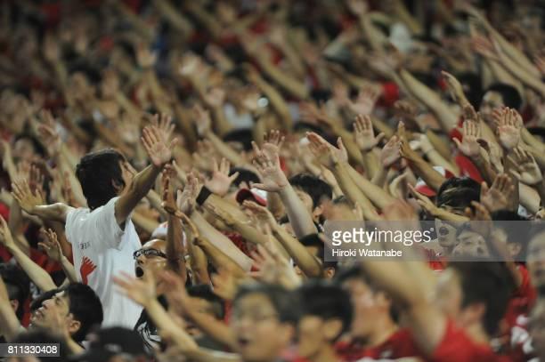 Fans of Urawa Red Diamonds cheer during the JLeague J1 match between Urawa Red Diamonds and Albirex Niigata at Saitama Stadium on July 9 2017 in...