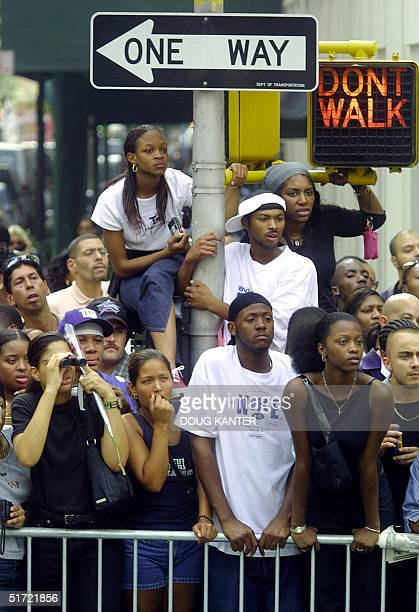 Fans of US pop singer Aaliyah watch from across the street from the St Ignatius Loyola Church following funeral services in New York on 31 August...