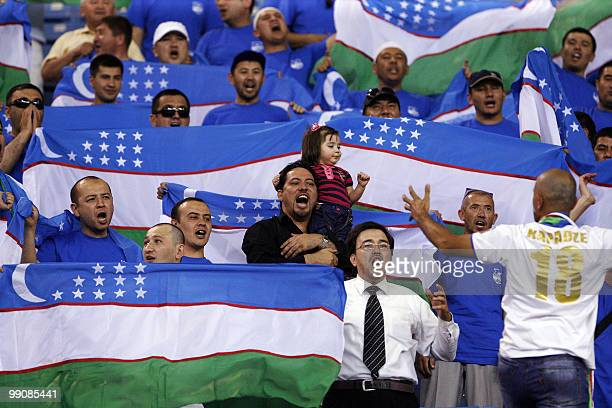 Fans of Uzbekistan's Bunyodkor cheer for their team before the start of their AFC Champions League round of 16 football match against Saudi Arabia's...