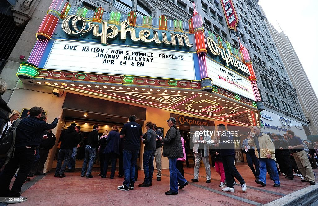 Fans of veteran French rocker Johnny Hallyday enter the Orpheum Theatre for his first concert in two years on April 24, 2012 in Los Angeles, California, where Hallyday begins a comeback tour two years after a health scare which nearly killed him in his adopted home of Los Angeles. In a tribute to the city 'where they saved my life,' the 68-year-old will start the more than 50-show tour aiming to 'make the public tremble with emotion,' he told AFP earlier this month. AFP PHOTO/Frederic J. BROWN