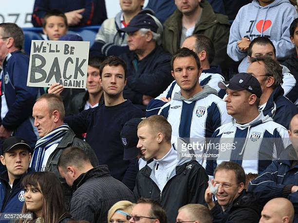 Fans of West Bromwich Albion hold up a sign saying We'll Be Back Again following their 02 defeat to Liverpool and relegation out of the Barclays...