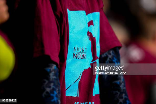 Fans of West Ham United wear commemorative tshirts to mark the 25 year anniversary of the Legend Bobby Moore during the Premier League match between...