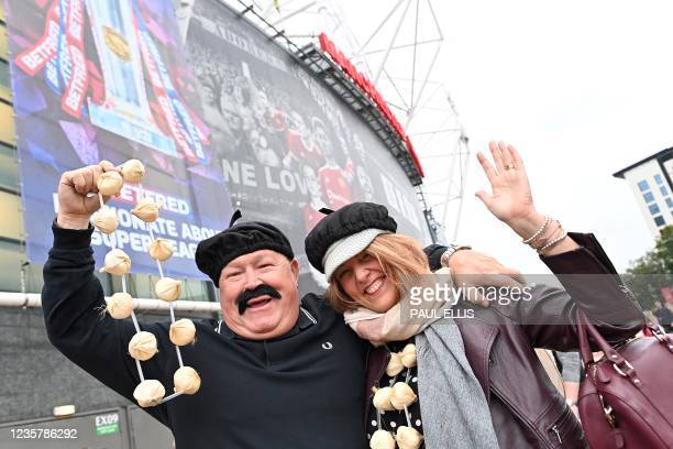Fans of Wigan Warriors wearing berrets and a string of onions, arrive to support the Catalans Dragons ahead of the Super League Grand Final rugby...