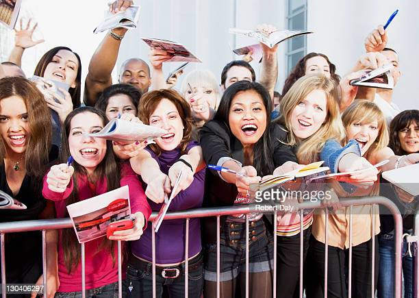 fans offering notepads for celebrity's signature behind barrier - beroemdheden stockfoto's en -beelden
