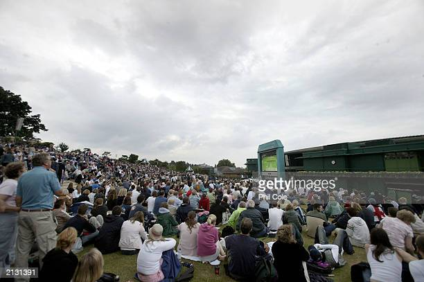 Fans on Henman Hill watch Tim Henman of Great Britain in action against Sebastien Grosjean of France during the men's quarter finals at the Wimbledon...