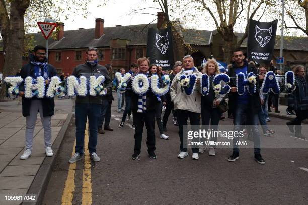 Fans on the 5000/1 walk with flowers saying Thank You Vichai make their way to the King Power stadium during the Premier League match between...