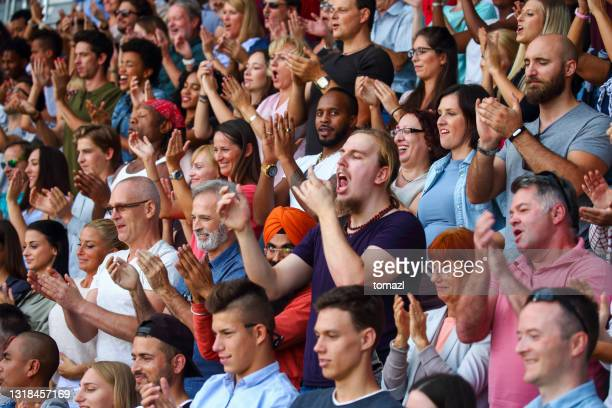 fans on the stadium cheering and clapping - fan enthusiast stock pictures, royalty-free photos & images