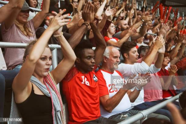 fans on the stadium cheering - spectator stock pictures, royalty-free photos & images