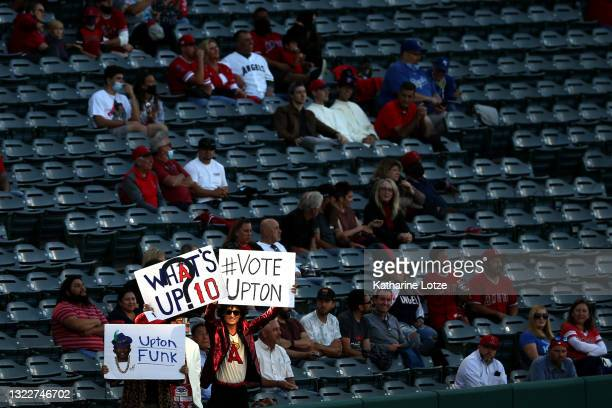 Fans outfield Justin Upton of the Los Angeles Angels hold signs in the stands along the third base line during a game between the Los Angeles Angels...