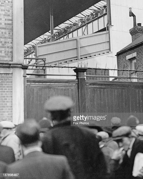 Fans outside White Hart Lane football ground look on as German supporters in the stands give the Nazi salute before an England-Germany football...
