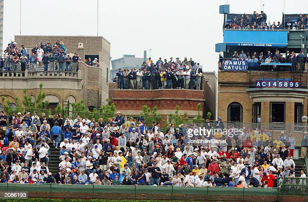 Fans pack the right field bleechers and the rooftops across the street from Wrigley Field for the MLB Interleague game between the Chicago Cubs and...