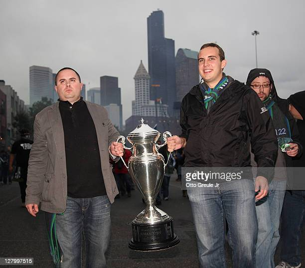 Fans participate in the March to the Match while holding the Sounders' 2009 US Open Cup trophy prior to the match between the Seattle Sounders FC and...
