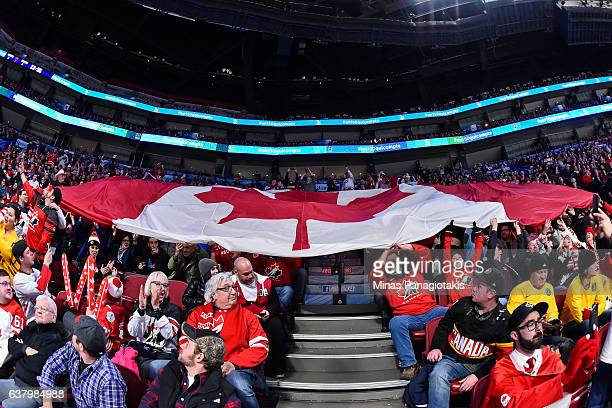 Fans pass on a giant Canadian flag during the 2017 IIHF World Junior Championship semifinal game between Team Canada and Team Sweden at the Bell...