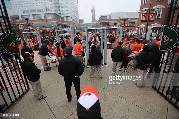 Fans pass through metal detectors upon entering the stadium prior to the Toronto Blue Jays and Baltimore Orioles home opener at Oriole Park at Camden...