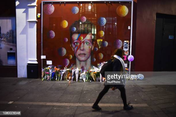 Fans pay tributes with flowers candles and photos of David Bowie in Brixton London on January 10 2019 The iconic British musician died two days after...