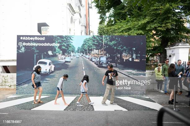 Fans pose against a recreation of the pedestrian crossing outside Abbey Road studios fifty years since the iconic album cover for Abbey Road by the...