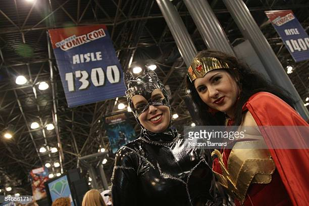 Fans pose as their favorite comic book and science fiction characters 'Cat Woman' and 'Wonder Woman' at the 2009 New York Comic Con at the Jacob...