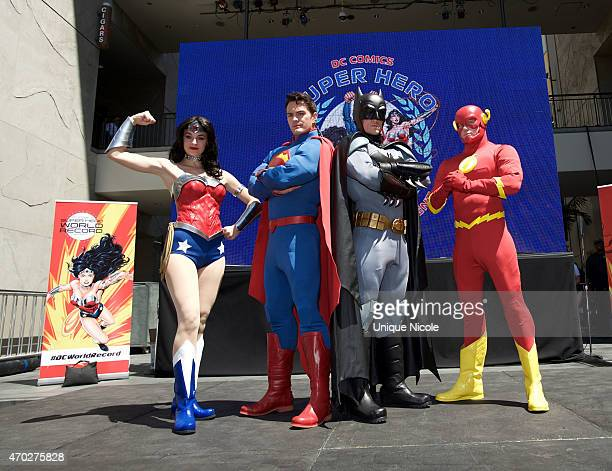 Fans pose dressed as DC Comics Super Heroes at the DC Comics Super Hero World Record Event at the Hollywood Highland Center on April 18 2015 in Los...