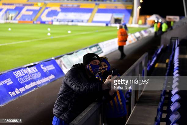 Fans pose for a photo inside the stadium prior to the Sky Bet League One match between Shrewsbury Town and Accrington Stanley at Montgomery Waters...