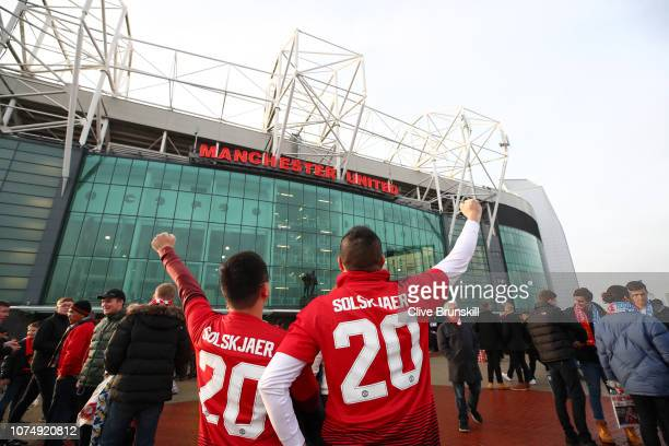 Fans pose for a photo wearing a shirt with the name of Ole Gunnar Solskjaer Interim Manager of Manchester United as they make their way to the...