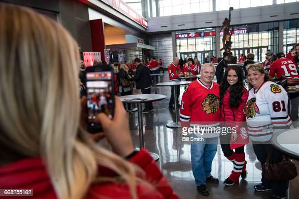 Fans pose for a photo with a Chicago Blackhawks ice crew member prior to Game One of the Western Conference First Round between the Chicago...