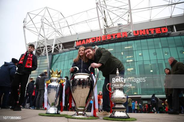 Fans pose for a photo with replicas of the Premier League Trophy The UEFA Champions League Trophy and the FA Cup Trophy outside the stadium prior to...