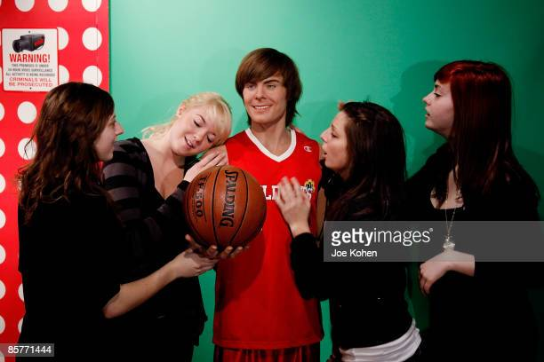 Fans pose for a photo with the newly unveiled wax figure of actor Zac Efron unveiled at Madame Tussauds on April 2 2009 in New York City