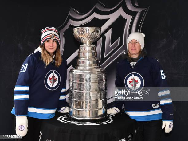 Fans pose for a photo with the Stanley Cup in The PreGame in advance of the 2019 Tim Hortons NHL Heritage Classic as the Calgary Flames take on the...