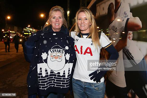 Fans pose for a photograph in their festive jumpers outside the stadium prior to the Premier League match between Tottenham Hotspur and Hull City at...