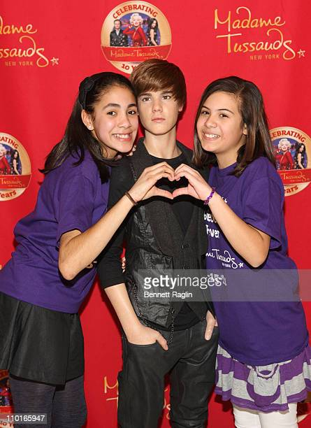 Fans pose for a picture with the Justin Bieber wax figure during the Justin Bieber wax figure unveiling at Madame Tussauds on March 15 2011 in New...