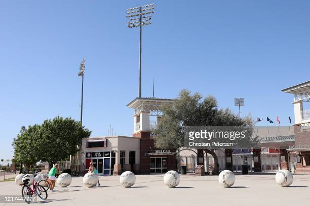 Fans pose for photographs outside of the Texas Rangers and Kansas City Royals spring training facility Surprise Stadium on April 07 2020 in Surprise...