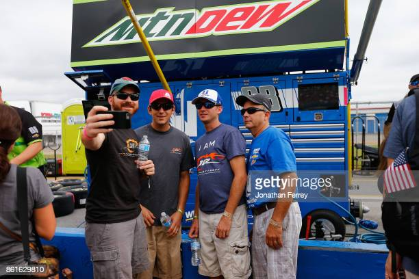 Fans pose for photos inthe pit box of Dale Earnhardt Jr driver of the Mountain Dew Chevrolet during the Monster Energy NASCAR Cup Series Alabama 500...
