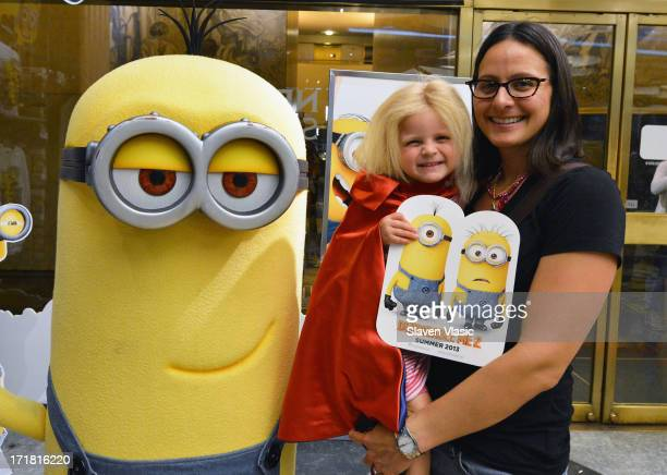 Fans pose for pictures at the Meet The Minions from 'Despicable Me 2' event at NBC Experience Store on June 28 2013 in New York City