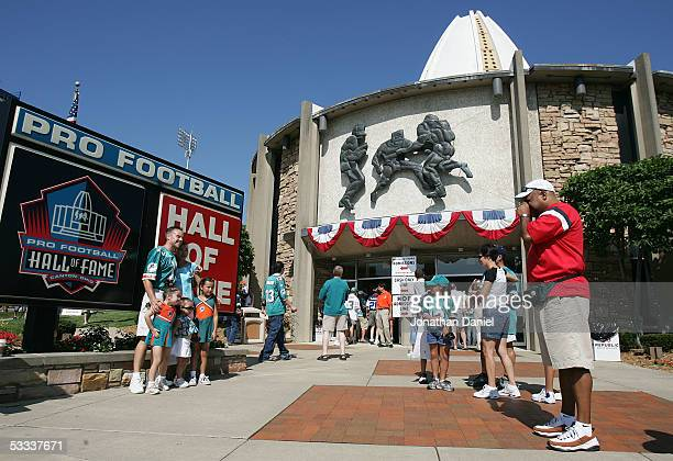 Fans pose for pictures in front of the Pro Football Hall of Fame before the 2005 NFL Hall of Fame enshrinement ceremony on August 7 2005 in Canton...