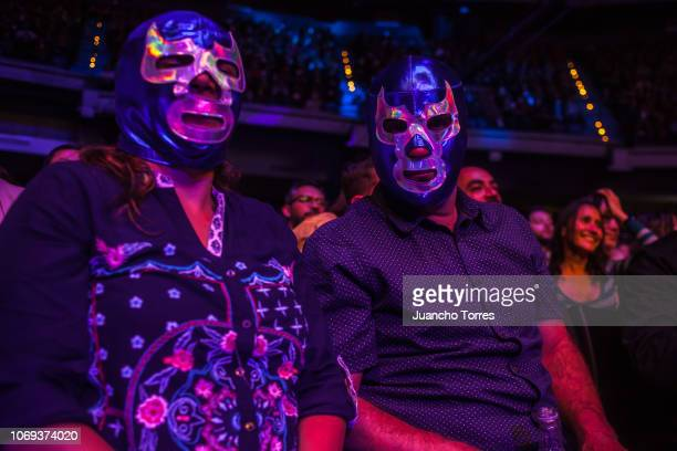 Fans pose for pictures wearing masks during an AAA World Wide Wrestling match on November 16 2018 in Bogota Colombia