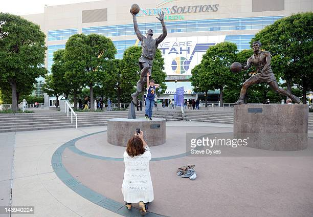 Fans pose in font of statues of Karl Malone and John Stockton before Game Three of the Western Conference Quarterfinals in the 2012 NBA Playoffs at...