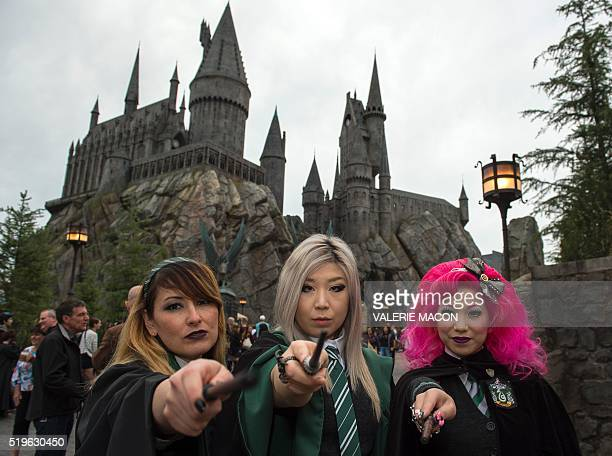 Fans pose in front of Hogwarts castle at the Grand Opening of the 'Wizarding World of Harry Potter' to the public at Universal Studios Hollywood in...