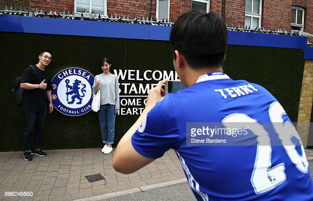Fans pose infront of the Chelsea badge during the Premier League match between Chelsea and Burnley at Stamford Bridge on August 27 2016 in London...