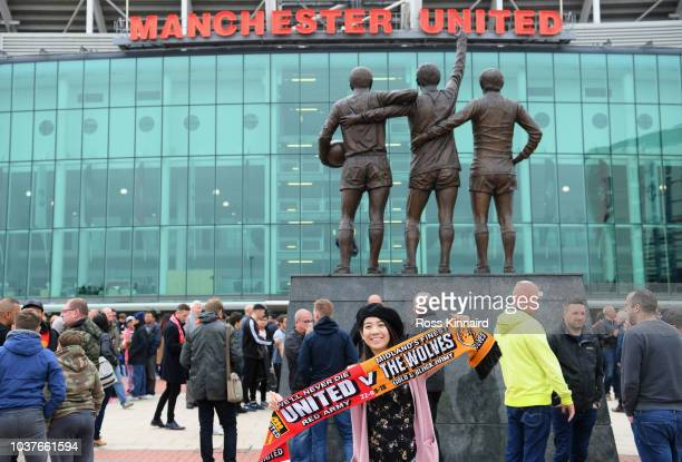 Fans pose infront of the United Trinity statue outside the ground prior to the Premier League match between Manchester United and Wolverhampton...